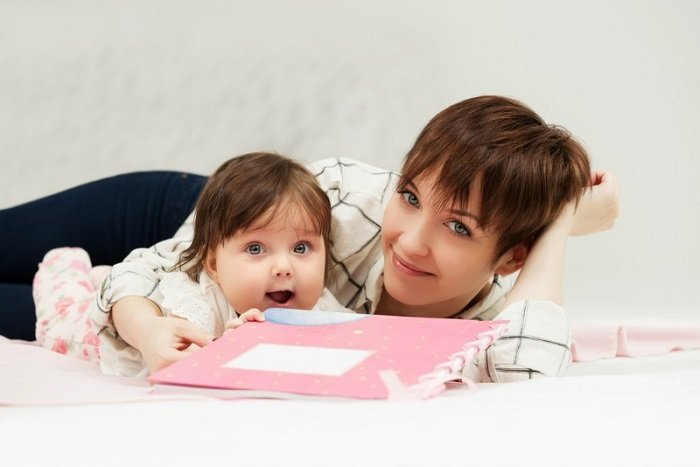 mẹ và bé nằm trên giường cầm sách màu hồng, đọc sách