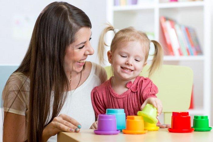 mẹ tóc nâu dài mặc áo trắng cười với bé tóc vàng buộc 2 bên mặc áo hồng chơi đồ chơi nhiều màu sắc bên bàn gỗ