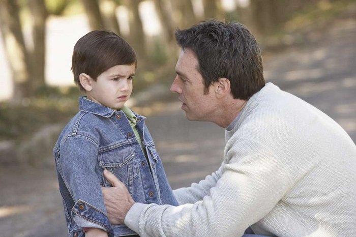 bố mặc áo xám ngồi xuống nói chuyện mặt nghiêm nghị với con trai mặc áo bò, giao tiếp phi ngôn ngữ