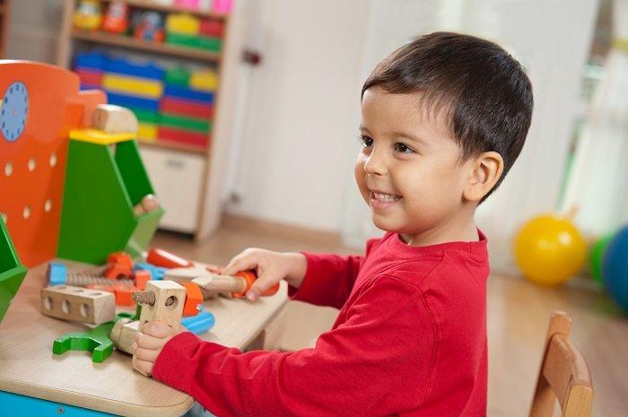 bé trai mặc áo đỏ tóc nâu cười, ngồi bên bàn đồ chơi nhiều màu sắc hình khối, giao tiếp phi ngôn ngữ