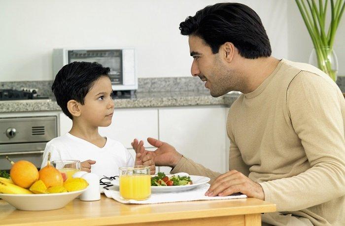 bố mặc áo be nói chuyện với bé trai mặc áo trắng trên bàn ăn trong nhà bếp, giao tiếp phi ngôn ngữ