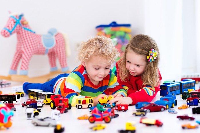 bé trai và bé gái nằm chơi đồ chơi dưới sàn, đồ chơi truyền thống, đồ chơi công nghệ
