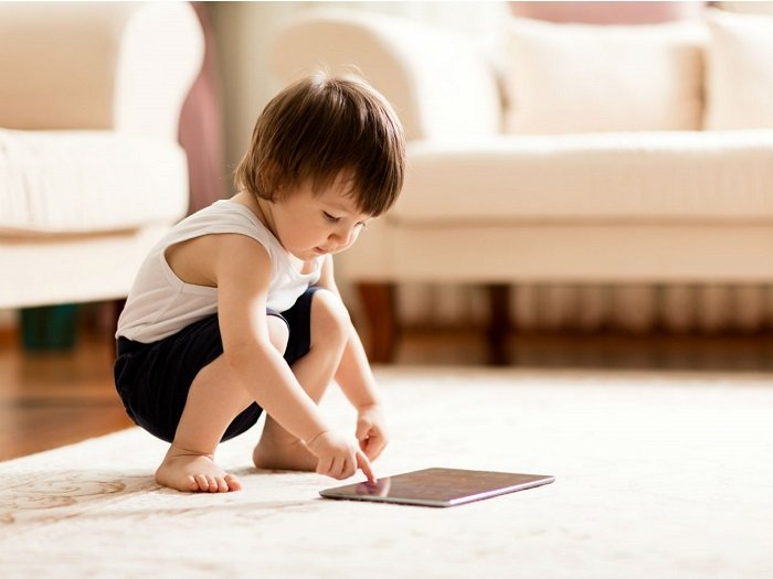 bé trai chơi máy tính bảng dưới sàn nhà