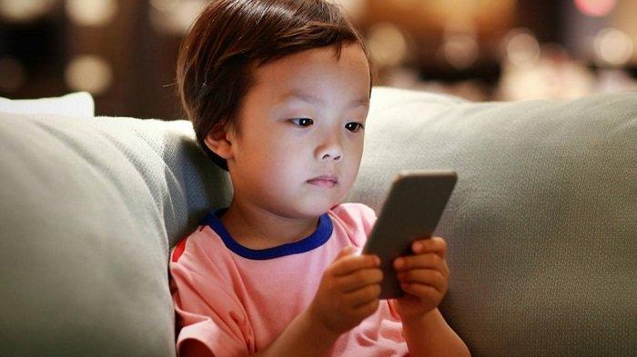 bé trai chơi điện thoại trên ghế sofa