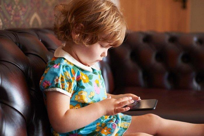 bé gáingồi chơi điện thoại trên ghế sofa