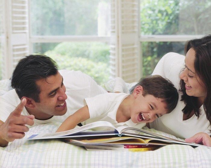 bố mẹ và con trai cười với nhau, nằm trên giường, cầm cuốn sách, phát triển ngôn ngữ, trẻ 1-3 tuổi