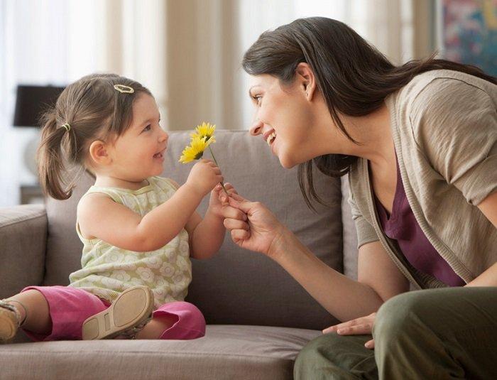 mẹ tặng hoa và cười với con gái, ngồi trên ghế sofa
