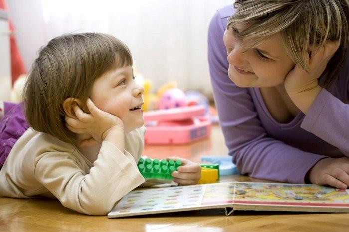 mẹ và con trai nằm trên sàn nhà, cười cùng nhau bên cạnh cuốn sách
