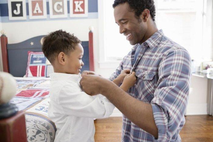 bố giúp đỡ con cài nút áo để khuyến khích con có hành động tốt