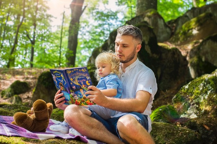 bố đọc sách cho con gái trong vườn cây
