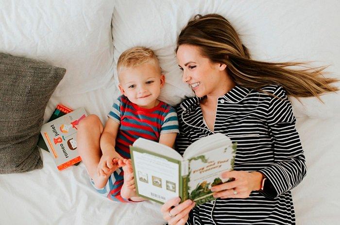 mẹ cùng bé nằm trên giường đọc sách