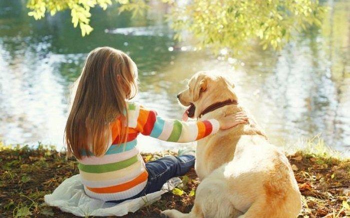 em nhỏ ngồi cạnh chó bên hồ