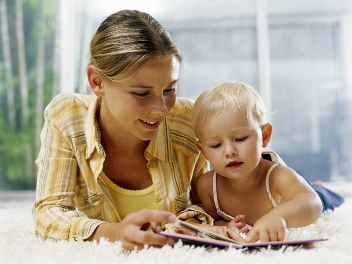 mẹ đọc sách cho bé ở trên giường