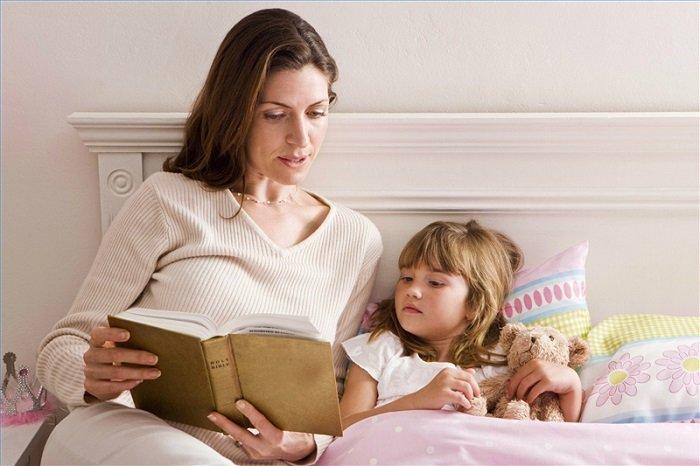 mẹ đọc sách cho con gái trên giường