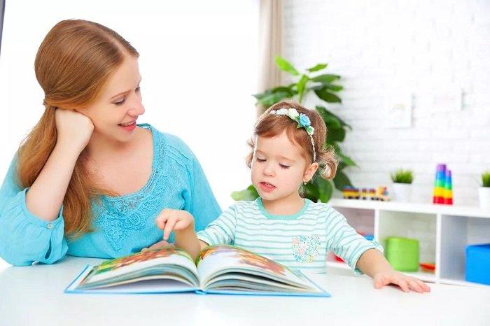 mẹ đọc sách cùng con gái bên bàn