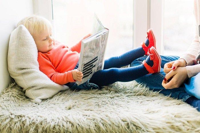 em nhỏ nằm trên giường đọc sách