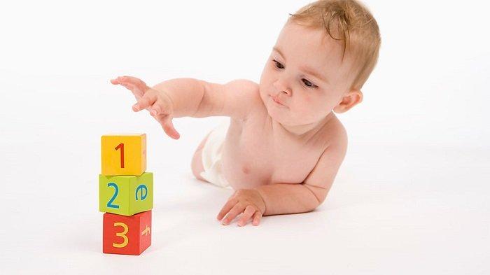 Bé 1 tuổi chơi xếp tháp để tăng cường nhận thức.