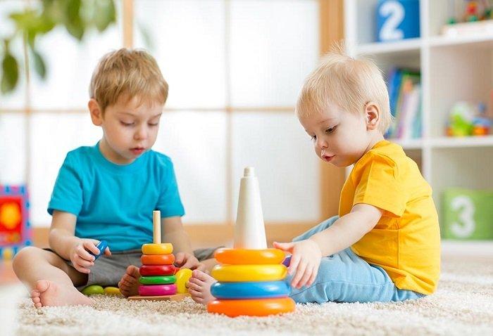 hai bé trai ngồi chơi đồ chơi, phát triển ngôn ngữ