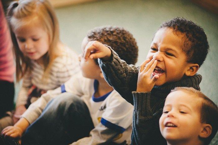 bé ngồi cùng các bạn vui vẻ, phát triển ngôn ngữ