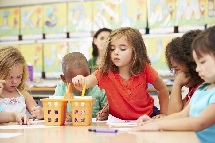 bé ngồi bên bàn học cùng các bạn, phát triển ngôn ngữ