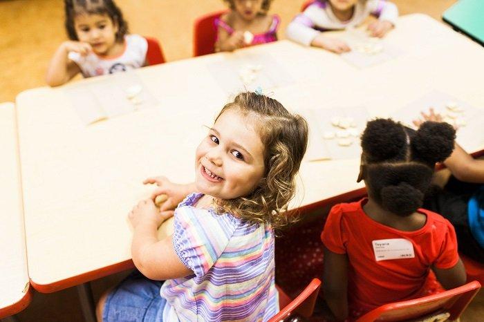 bé gái ngồi học vui vẻ cùng các bạn, phát triển ngôn ngữ
