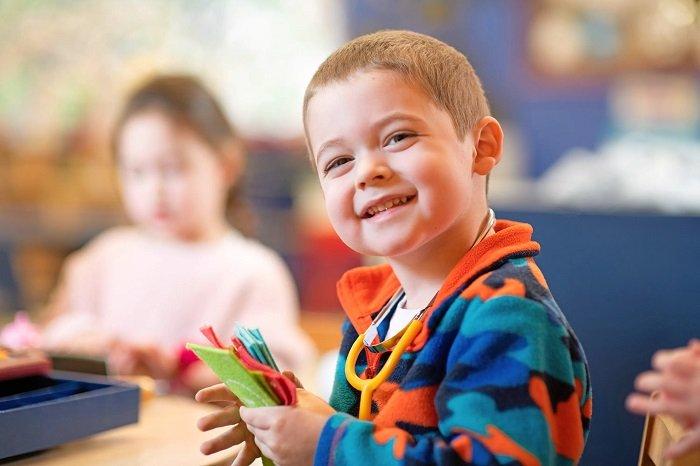 bé trai cầm đồ thủ công và cười, phát triển ngôn ngữ