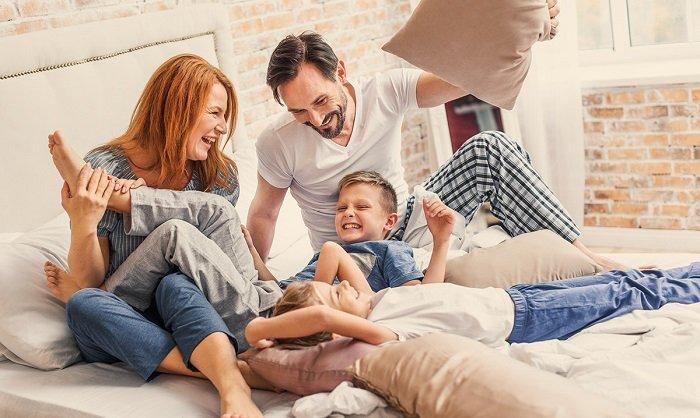 bố mẹ và bé vui đùa trên giường, trò chuyện và lắng nghe