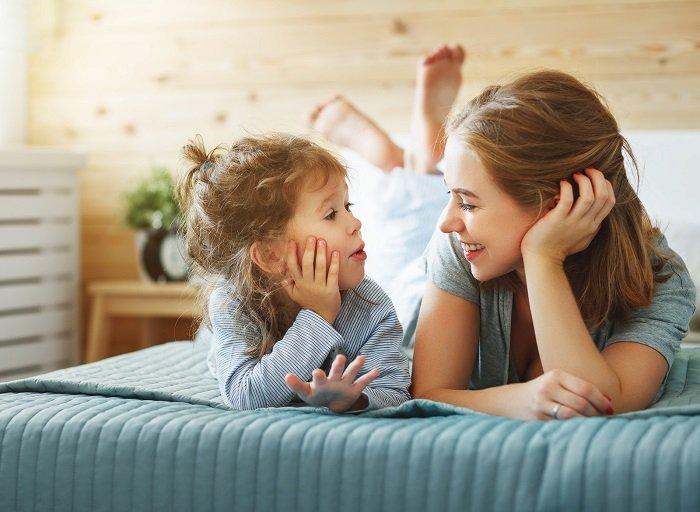 mẹ và bé trò chuyện trên giường