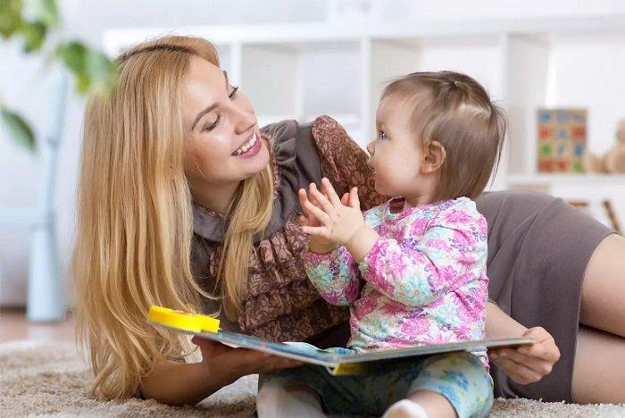 mẹ đọc sách cho bé gái trên ghế sofa