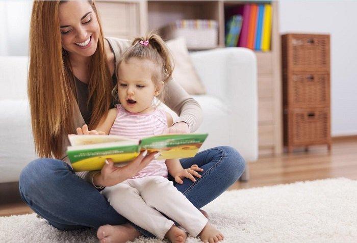 mẹ đọc sách cho con gái trên sàn nhà