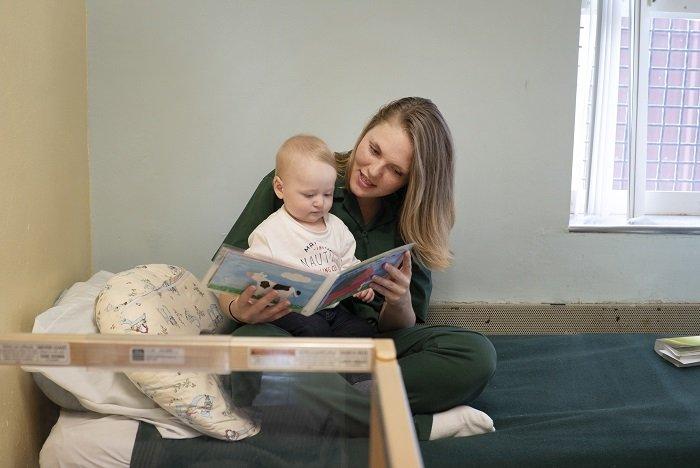 mẹ đọc sách cho bé trai trên giường