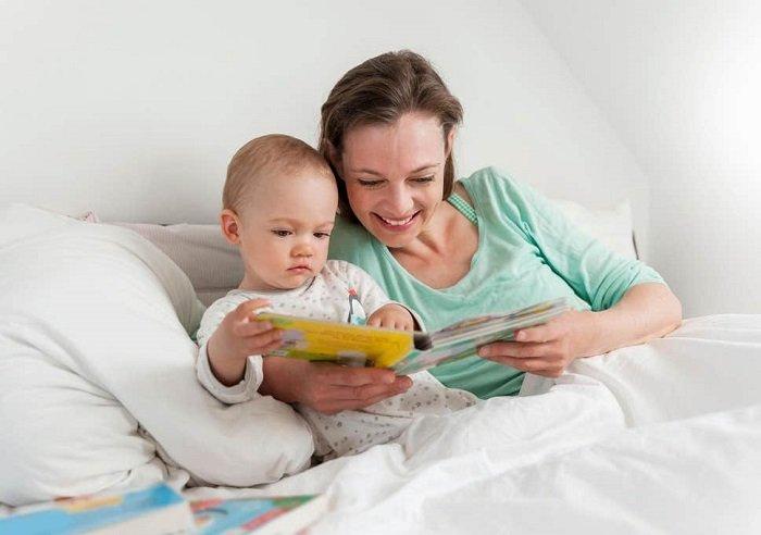 mẹ đọc sách cho con trai trên giường, phát triển ngôn ngữ