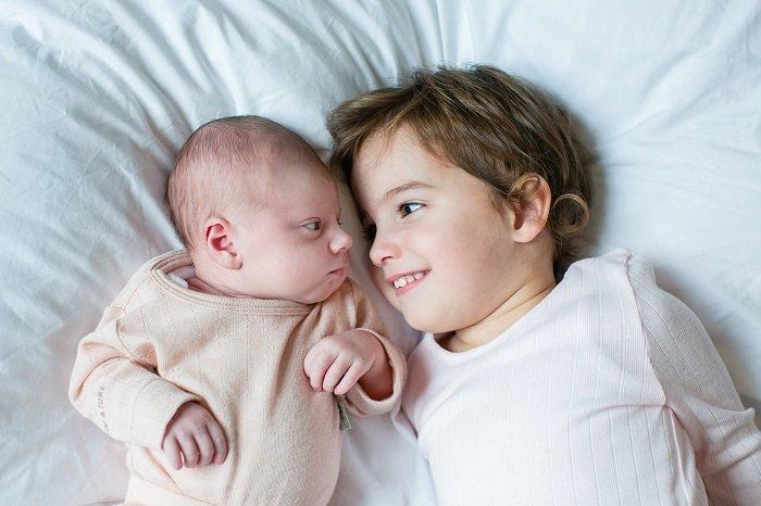 bé trai nằm trên giường cùng em bé sơ sinh, phát triển ngôn ngữ