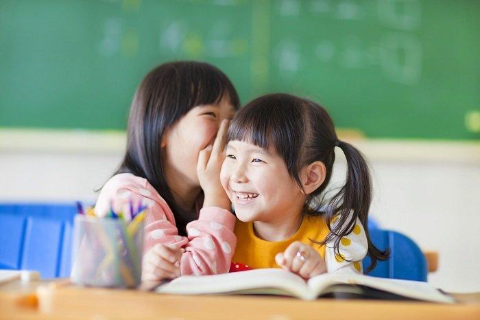 bé thì thầm với bạn trong lớp học, trẻ nói quá nhiều