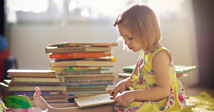 bé gái đọc sách trên sàn nhà, trẻ gặp vấn đề về kỹ năng đọc