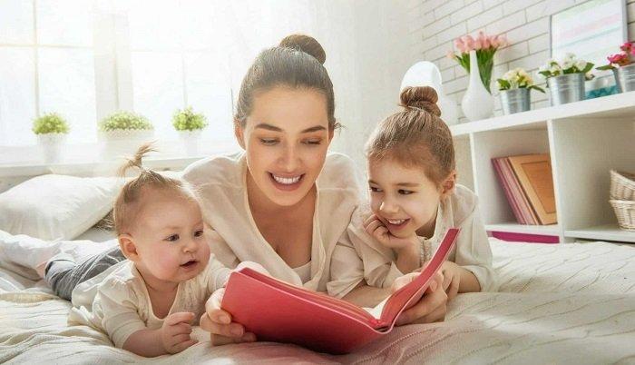 mẹ và hai con nằm trên giường đọc sách dưới ánh nắng chiếu qua cửa sổ, phát triển ngôn ngữ