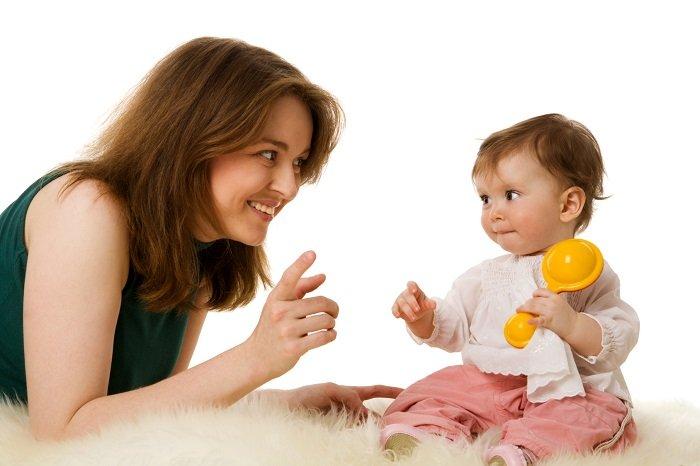 mẹ cười với bé trai đang cầm đồ chơi ngồi trên giường, phát triển ngôn ngữ