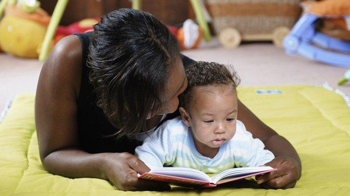 mẹ cùng con gái nhỏ nằm trên sàn đọc sách