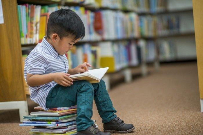 bé đọc sách trong thư viện, phát triển kỹ năng đọc của trẻ