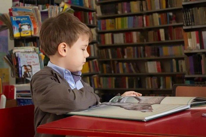 bé trai đọc sách, phát triển kỹ năng đọc của trẻ.