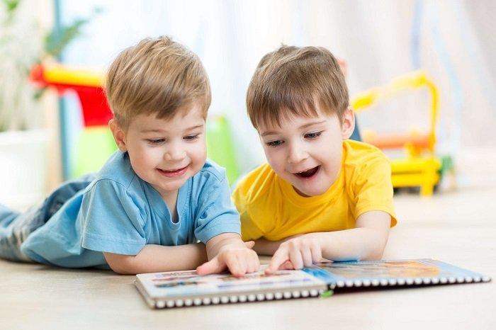 trẻ học song ngữ, bé trai đọc sách cùng bạn