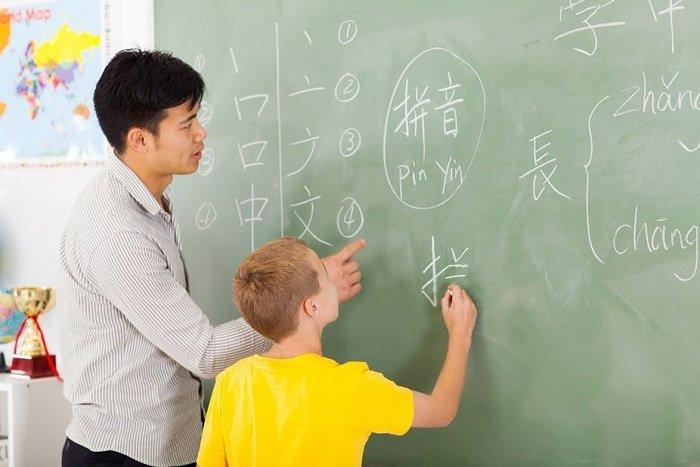 học sinh viết bảng, trẻ học song ngữ