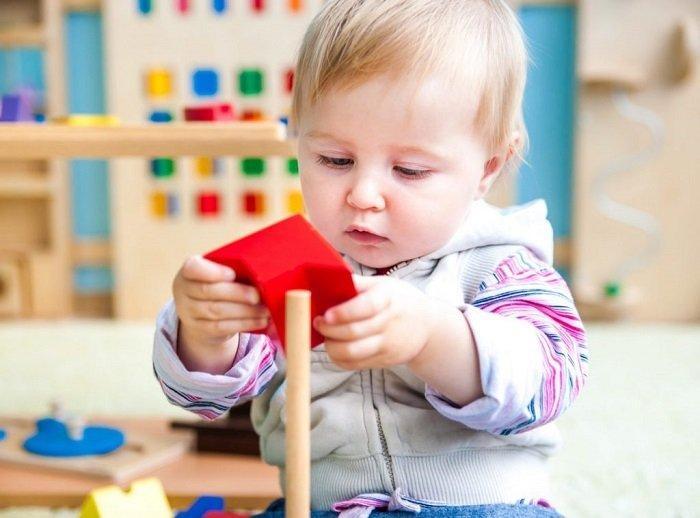 trẻ tập trung chơi đồ chơi