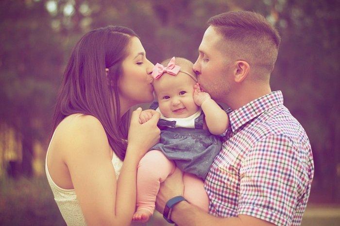Hai bố mẹ ôm hôn em bé