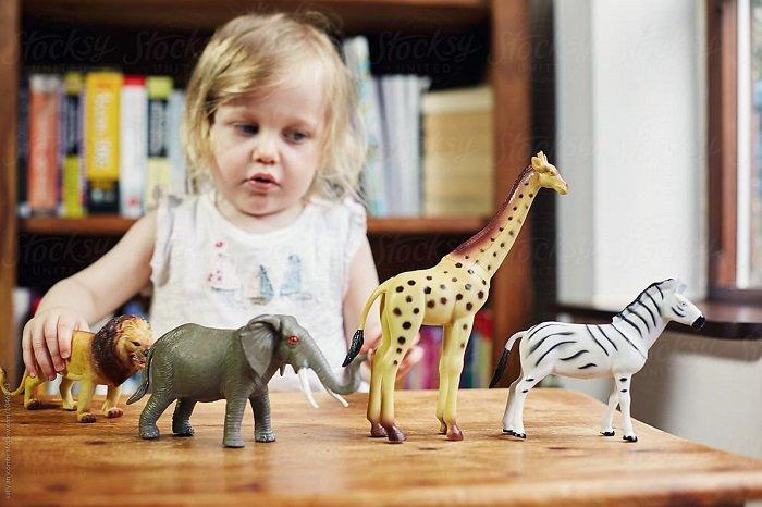 bé gái chơi đồ chơi con vật