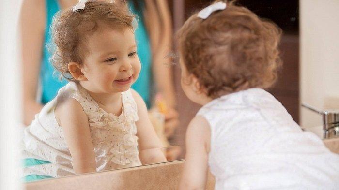 bé gái cười trước gương