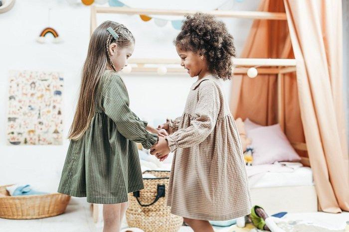 Hai em bé gái đang tương tác với nhau trong lớp học.