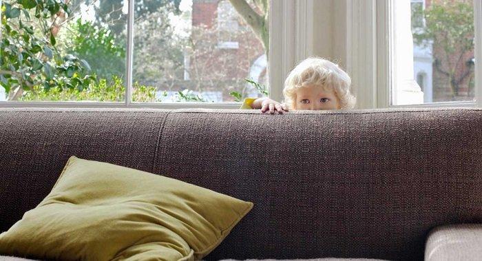 bé trốn sau ghế sô fa