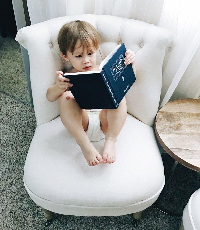 Em bé ngồi đọc sách.
