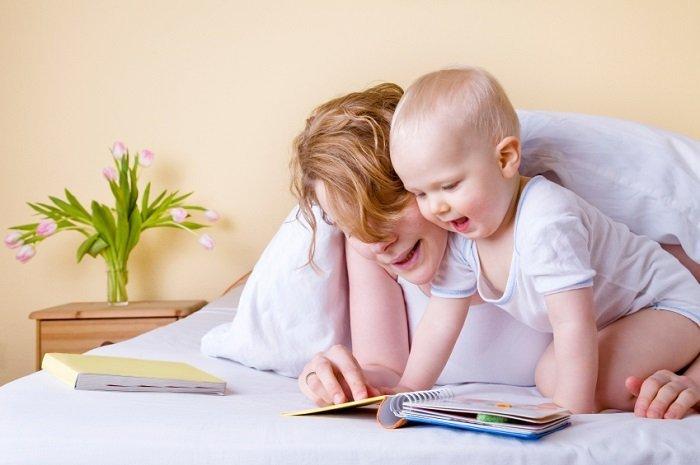 mẹ đọc sách cùng bé trai ở trên giường